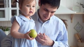 Dad and daughter in the kitchen, dad hugs daughter, daughter throws a green apple on the floor. Smiles, hugs, happy family stock video footage