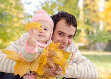 Dad and daughter with leaves. In autumn park royalty free stock photography