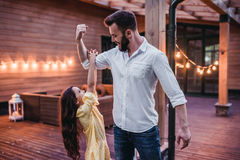 Dad with daughter. Little daughter is hanging on father`s hand on terrace Royalty Free Stock Photos