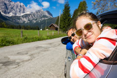 Dad and daughter looking out the car. Happy dad and daughter looking out the car window and mountains in the background. Dolomites, Italy royalty free stock images
