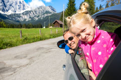 Dad and daughter looking out the car. Happy dad and daughter looking out the car window and mountains in the background. Dolomites, Italy royalty free stock image