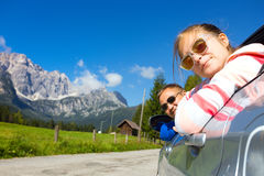 Dad and daughter looking out the car. Happy dad and daughter looking out the car window and mountains in the background. Dolomites, Italy stock images