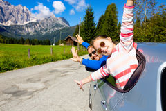 Dad and daughter looking out the car. Happy dad and daughter looking out the car window and mountains in the background. Dolomites, Italy stock image
