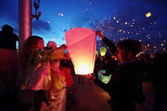 Dad and daughter with others launch lanterns Stock Photography