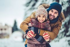 Dad with daughter outdoor in winter. Handsome young dad and his little cute daughter are having fun outdoor in winter. Enjoying spending time together. Family stock images