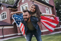 Dad with daughter outdoors. Dad and daughter are having fun on the backyard with american flag in hands and smiling royalty free stock photos