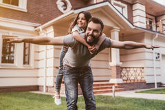 Dad with daughter outdoors. Dad and daughter having fun outdoors near their modern house on the background stock photos
