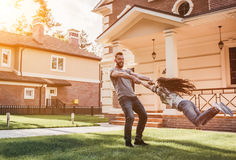 Dad with daughter outdoors. Dad and daughter having fun outdoors near their modern house on the background stock images