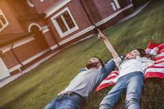 Dad with daughter outdoors. Dad and daughter are lying on american flag on the backyard stock image