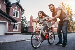 Dad with daughter outdoors. Dad is teaching daughter how to ride bicycle near their private house royalty free stock photo