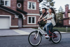 Dad with daughter outdoors. Dad is teaching daughter how to ride bicycle near their private house stock image