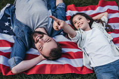Dad with daughter outdoors. Top view of dad and daughter are lying on the american flag and smiling stock images