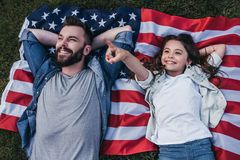 Dad with daughter outdoors. Top view of dad and daughter are lying on the americsn flag and smiling royalty free stock image