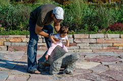 Dad and daughter play. Daddy puts his toddler girl on a stone turtle as they play in a local garden royalty free stock images
