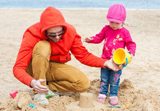 Father and his daughter playing on the beach. Dad and daughter playing on the beach in the sand stock photography