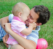 Dad and daughter. Playing lying on the grass in the park royalty free stock photography