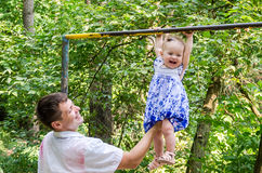 Dad and daughter playing in the park on a background of trees, baby girl hanging on the horizontal bar and the father of her suppo Stock Image