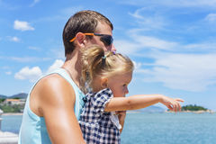 Dad and daughter playing on the promenade by the sea. young man, little girl Royalty Free Stock Photos