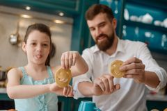 Dad and daughter playing. With smile cookies before baking them. Creative activity, culinary skills and fun time spent together royalty free stock images