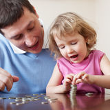 Dad and daughter puts coins Royalty Free Stock Photography