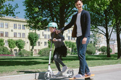 Dad and daughter ride a scooter and skate together.  Royalty Free Stock Photos