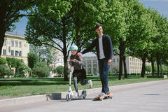 Dad and daughter ride a scooter and skate together Stock Photography