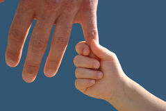 Dad and daughter's hand. A little girl is holding the finger of his dad's hand Stock Photo