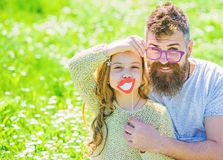 Dad and daughter sits on grass at grassplot, green background. Fatherhood concept. Family spend leisure outdoors. Child. And father posing with eyeglases and stock image