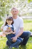 Father hugs his little daughter. Dad and daughter are sitting together in a city park royalty free stock image