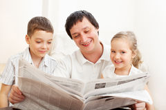 Dad with daughter and son reading newspaper Stock Images