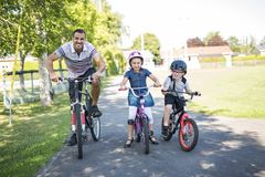 Dad With Daughter Son Riding Bikes In Park. A Dad With Daughter Son Riding Bikes In Park Royalty Free Stock Photography
