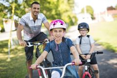 Dad With Daughter Son Riding Bikes In Park. A Dad With Daughter Son Riding Bikes In Park Stock Photo