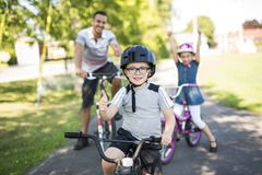 Dad With Daughter Son Riding Bikes In Park. A Dad With Daughter Son Riding Bikes In Park Stock Image