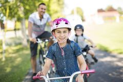 Dad With Daughter Son Riding Bikes In Park. A Dad With Daughter Son Riding Bikes In Park Stock Photos