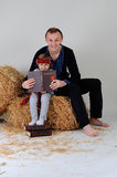 Dad and daughter in the Ukrainian national dress with a book abo. Dad and daughter in the Ukrainian national dress and jeans sitting on a haystack with a book of Royalty Free Stock Photo