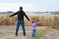 Dad and daughter watching as the plane prepares for takeoff Royalty Free Stock Images