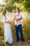 Dad and daughter watered belly pregnant mother on a summer day Royalty Free Stock Photo