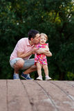 Dad with daughter on wooden bridge in park stock image
