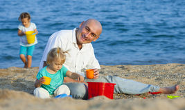 Dad and daughters  on  beach. Royalty Free Stock Image