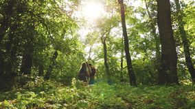 Dad and daughters, children travel in park in summer. teamwork travelers. Family on vacation travels in forest. friends