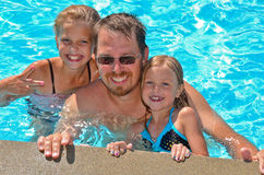 Dad with daughters in pool Royalty Free Stock Image