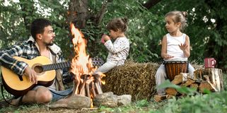 Dad with daughters rest in camping on the nature royalty free stock image
