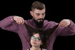 Dad is doing his daughter hair isolated on black background royalty free stock images