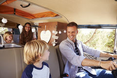 Dad driving family in a camper van, looking at his son Royalty Free Stock Images