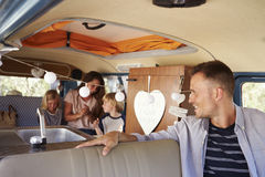 Dad in driving seat of camper van looks back at his family Stock Image