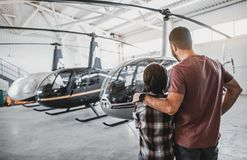Free Dad Embracing Child Looking At Modern Helicopter Royalty Free Stock Photography - 124151887