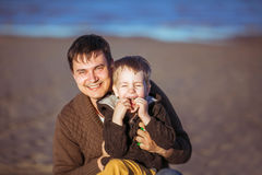 The dad is embracing his son, who's laughing. A young dark-haired men is smiling widely and embracing his five-year-old son, who's laughing, putting his fingers royalty free stock photo