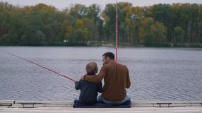 Dad encourages his son on fishing stock video footage