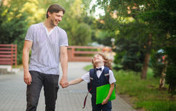 Dad escorted to school by his son. Stock Photo