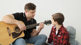 Dad explains to his son how to play guirat slowly front view slow motion stock footage